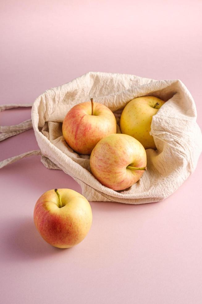 Manzanas en bolsa de supermercado textil reutilizable sobre fondo rosa foto
