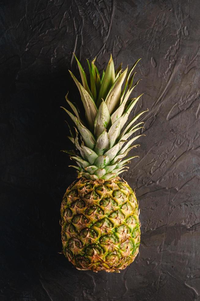 Pineapple on dark black textured background photo
