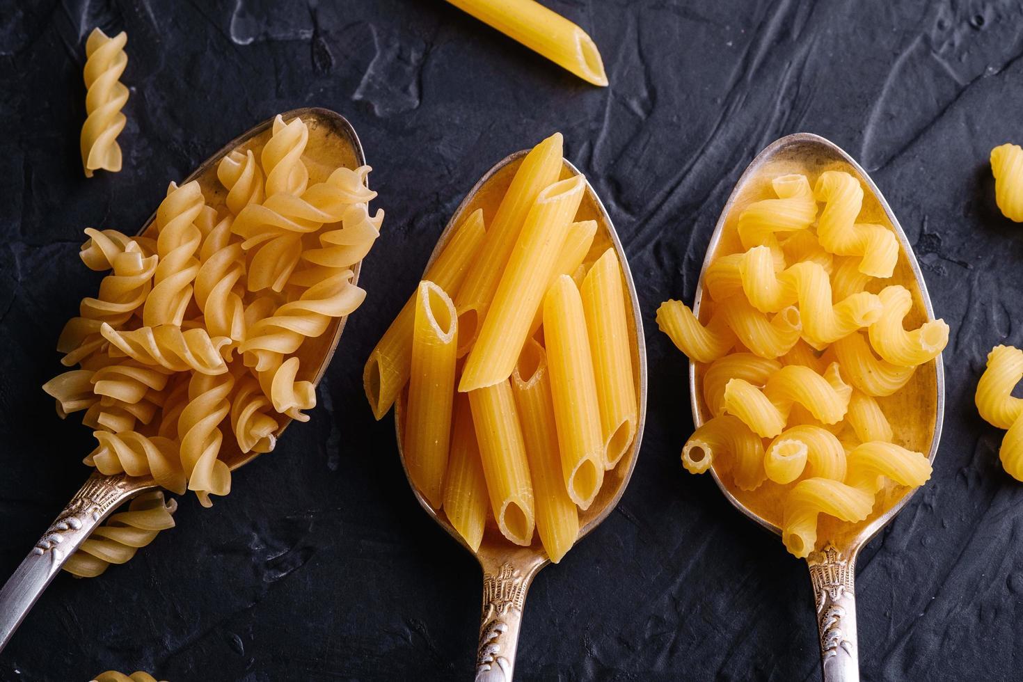 Tres cucharas de cubiertos con pasta cruda sobre fondo negro oscuro con textura foto