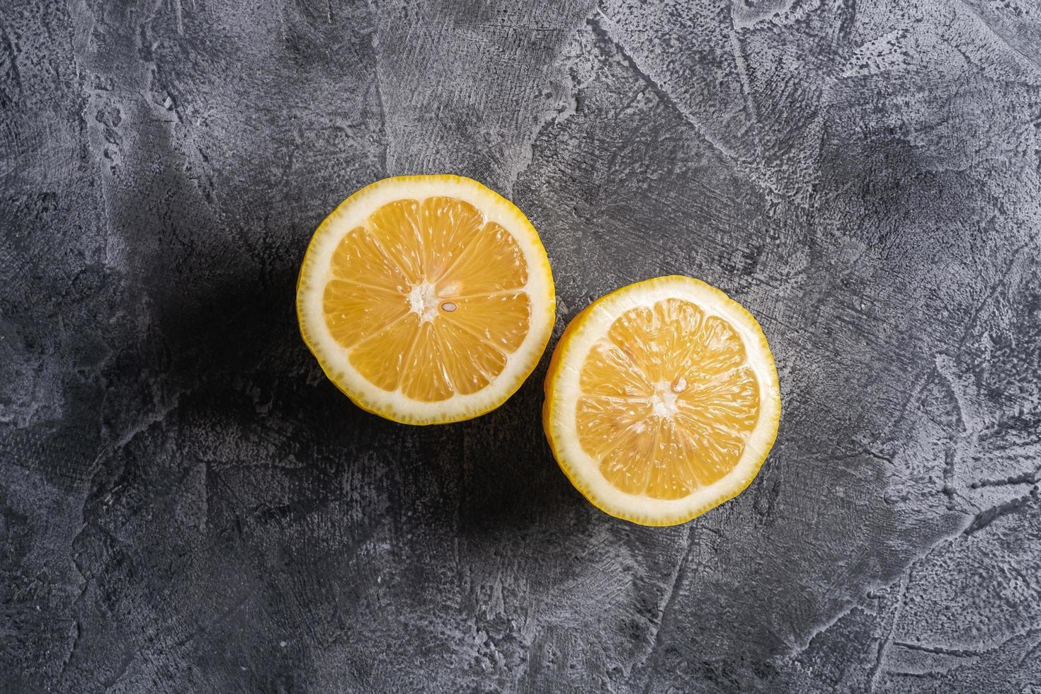 A lemon cut in half on gray concrete background photo