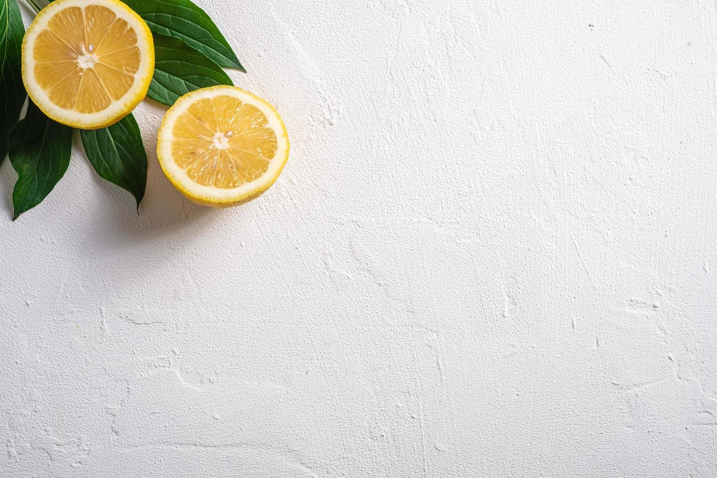 Two lemon slices with green leaves on white concrete background photo