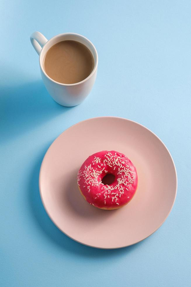 Pink donut with sprinkles on plate next to coffee photo