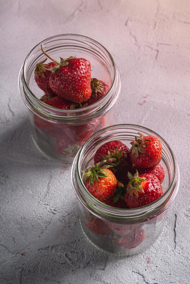 Fresas maduras frescas en dos frascos de vidrio sobre fondo neutro foto