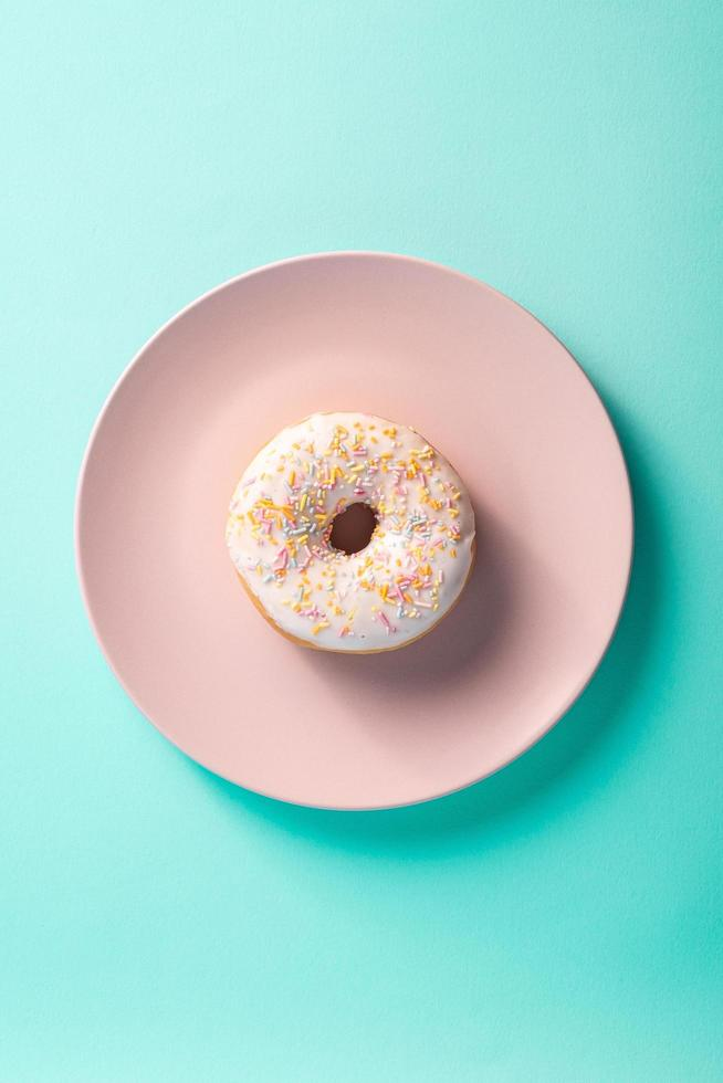 Vanilla donut with sprinkles on pink plate photo