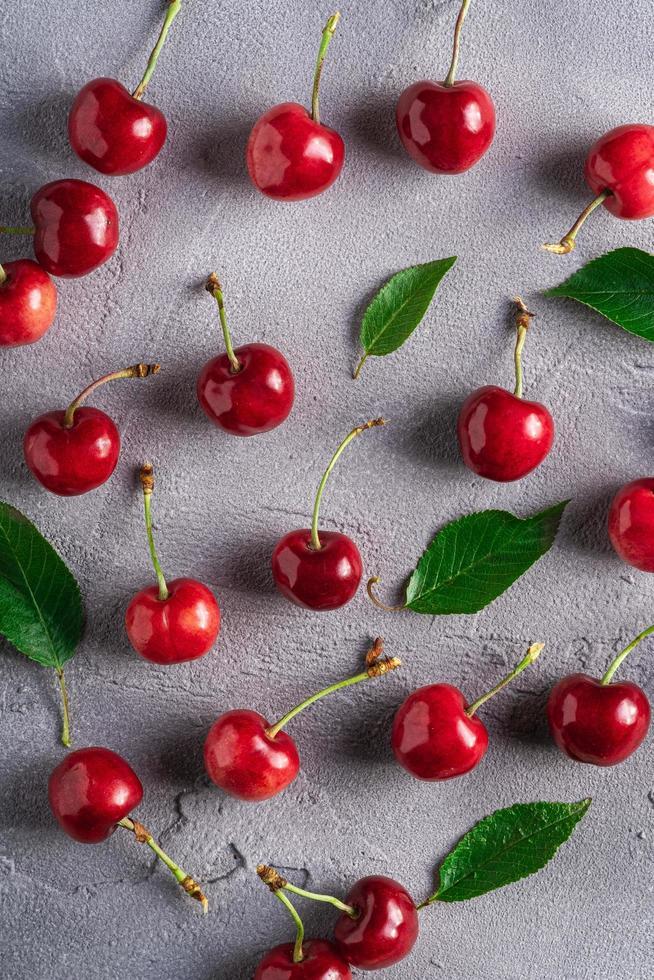 cerezas maduras frescas con hojas verdes foto