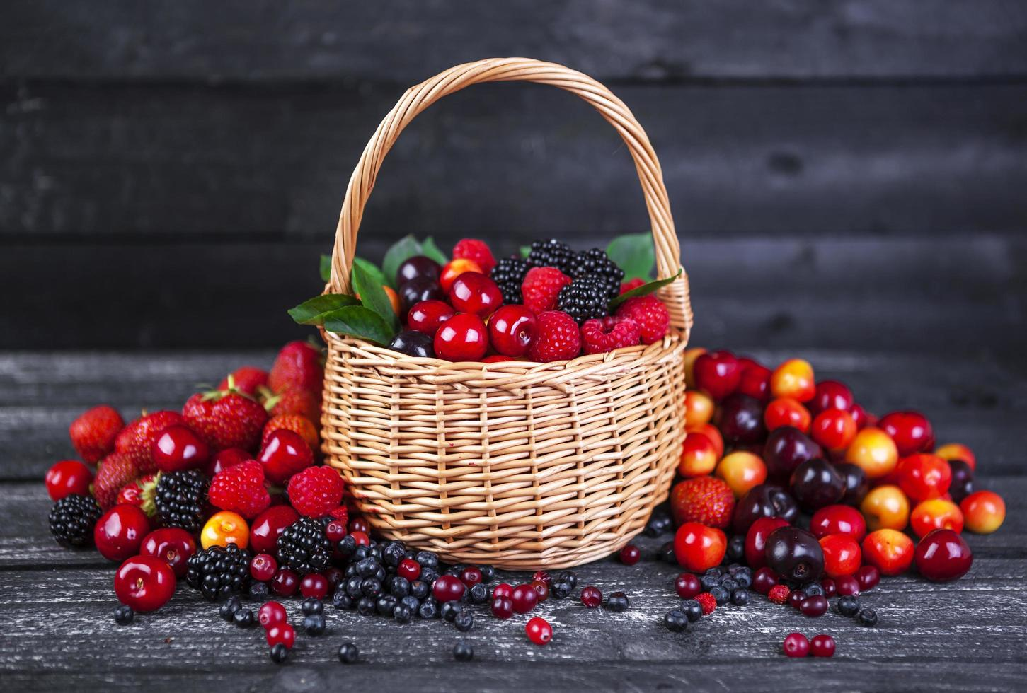 Mixed berries in basket on dark wooden background photo