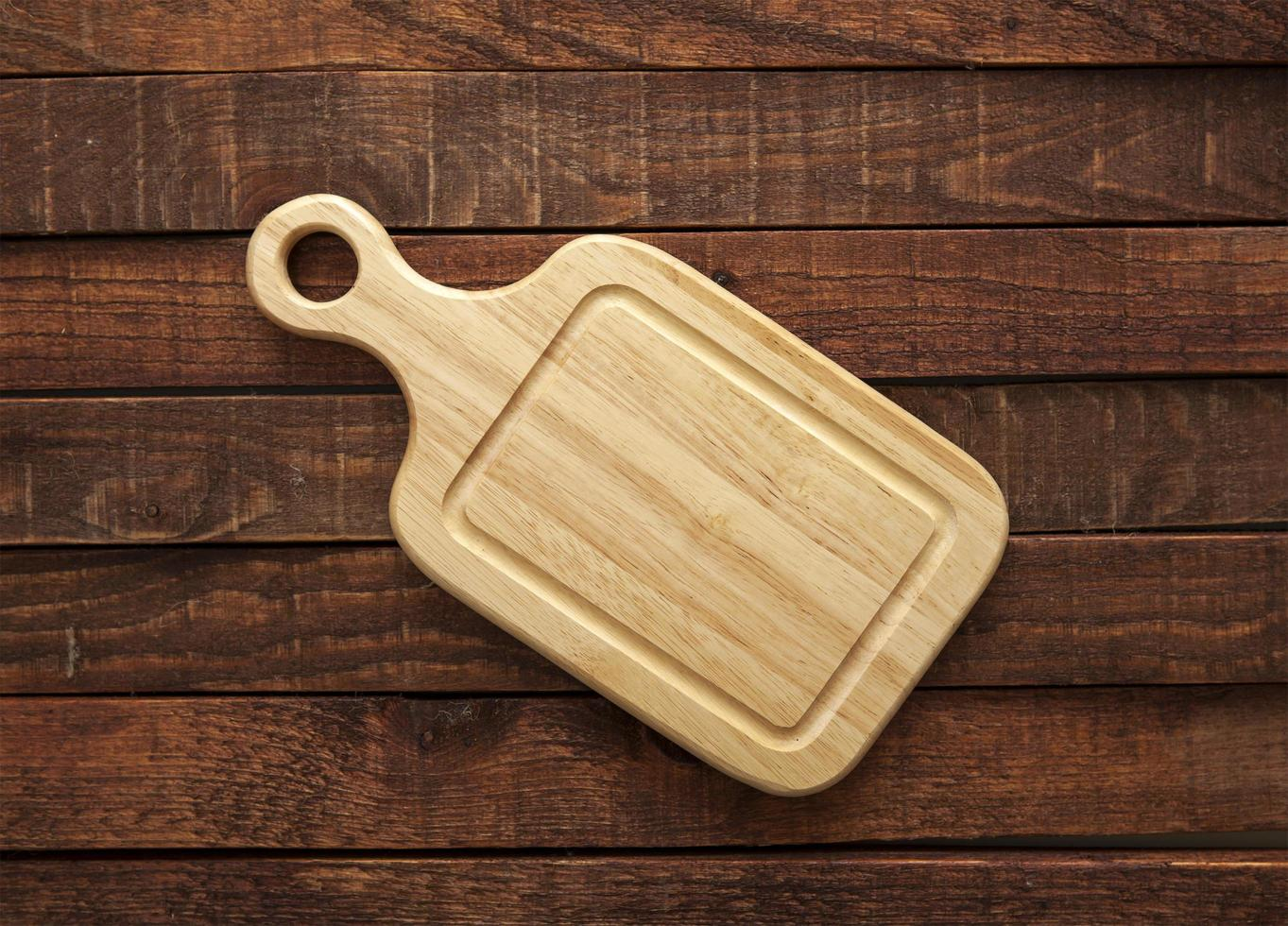 Cutting board on wooden table photo