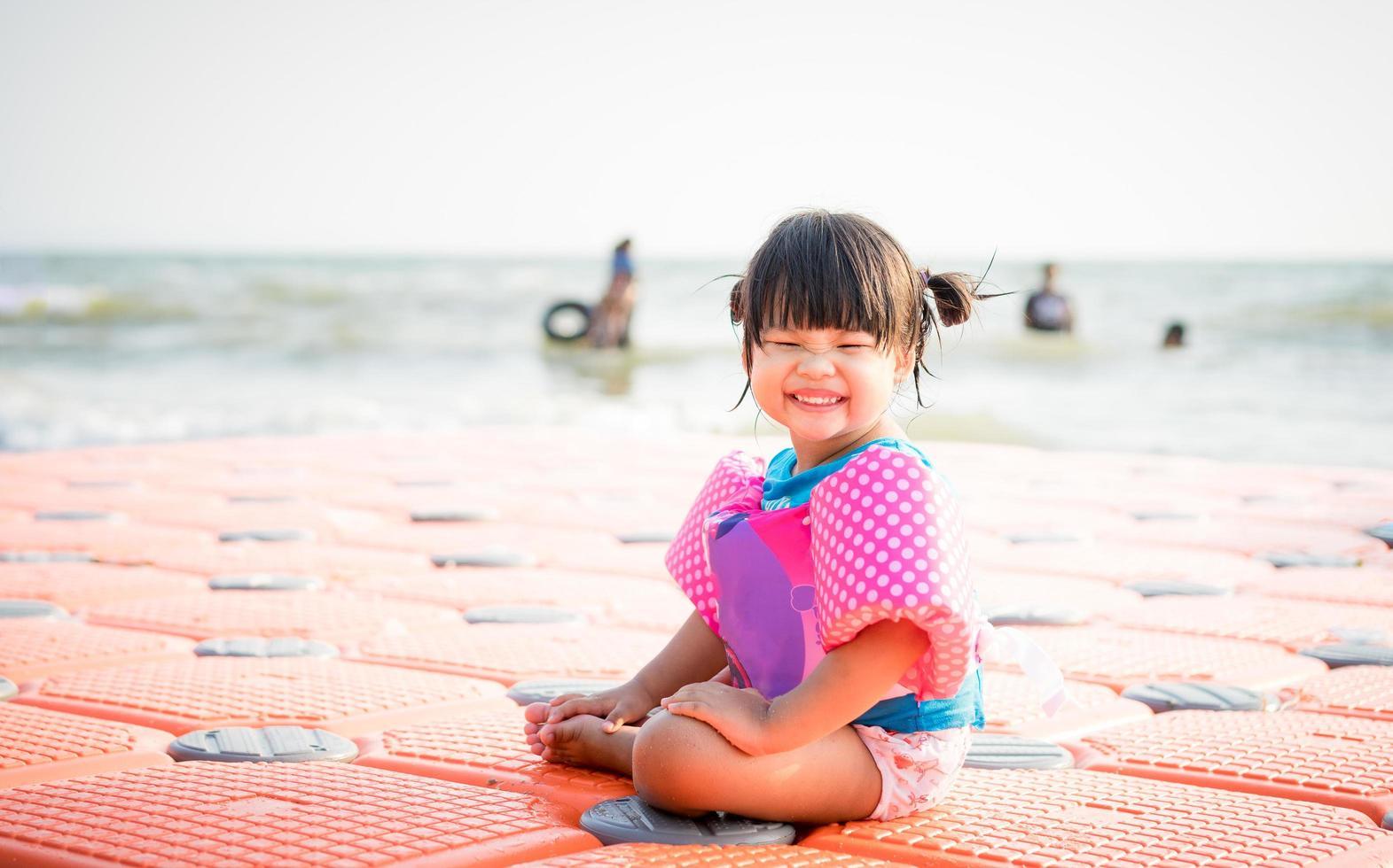 niña asiática sonriendo en la playa foto