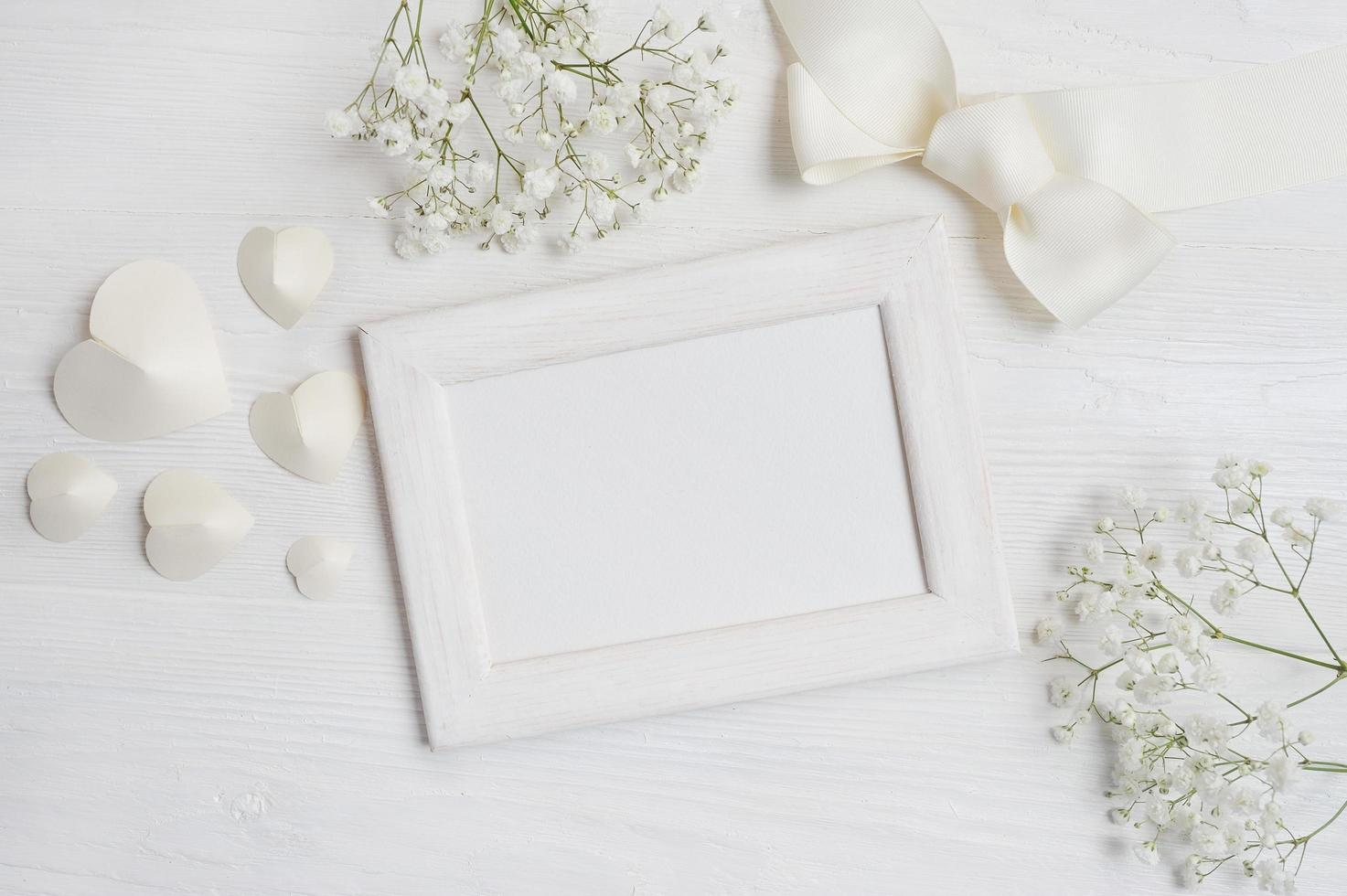 White wooden frame with hearts and flowers photo