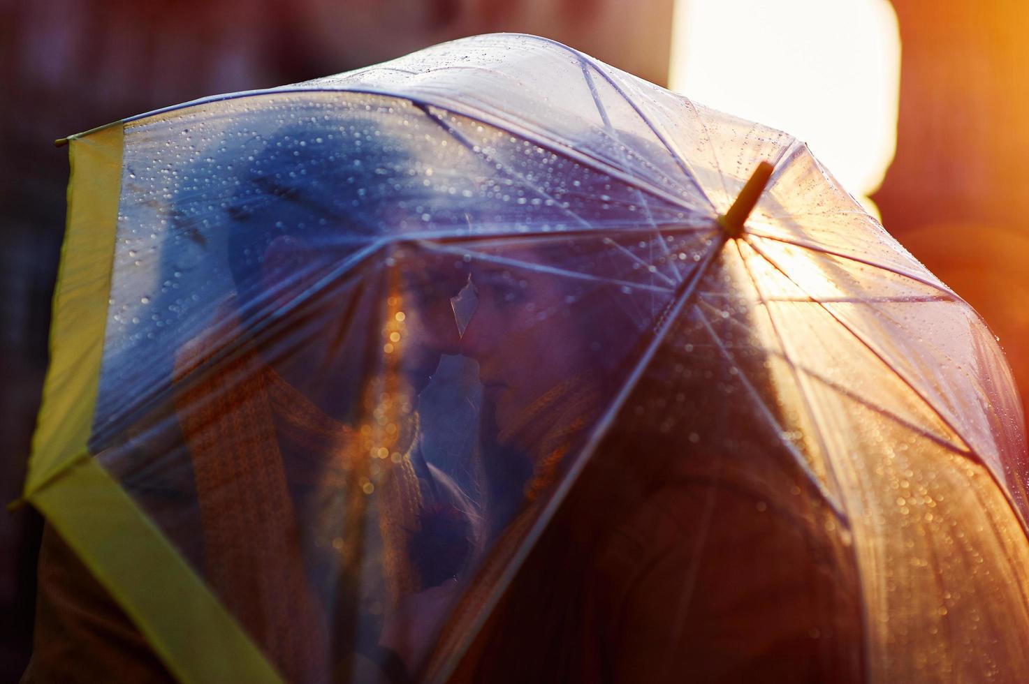 Closeup of young beautiful couple kissing under umbrella photo