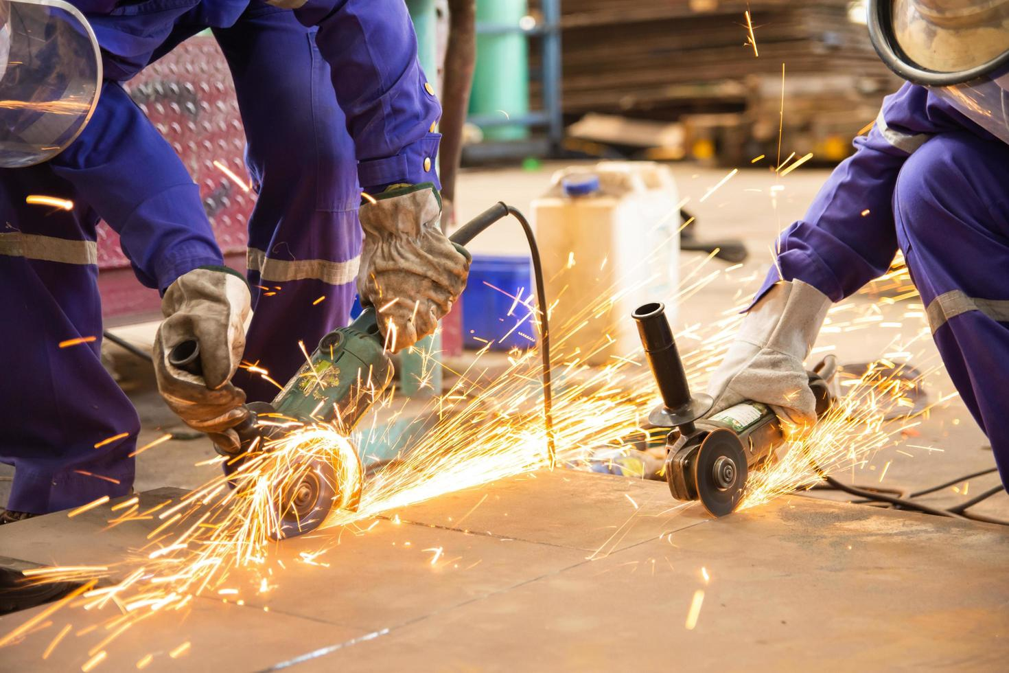 Workers cutting metal sheet with electric grinder photo