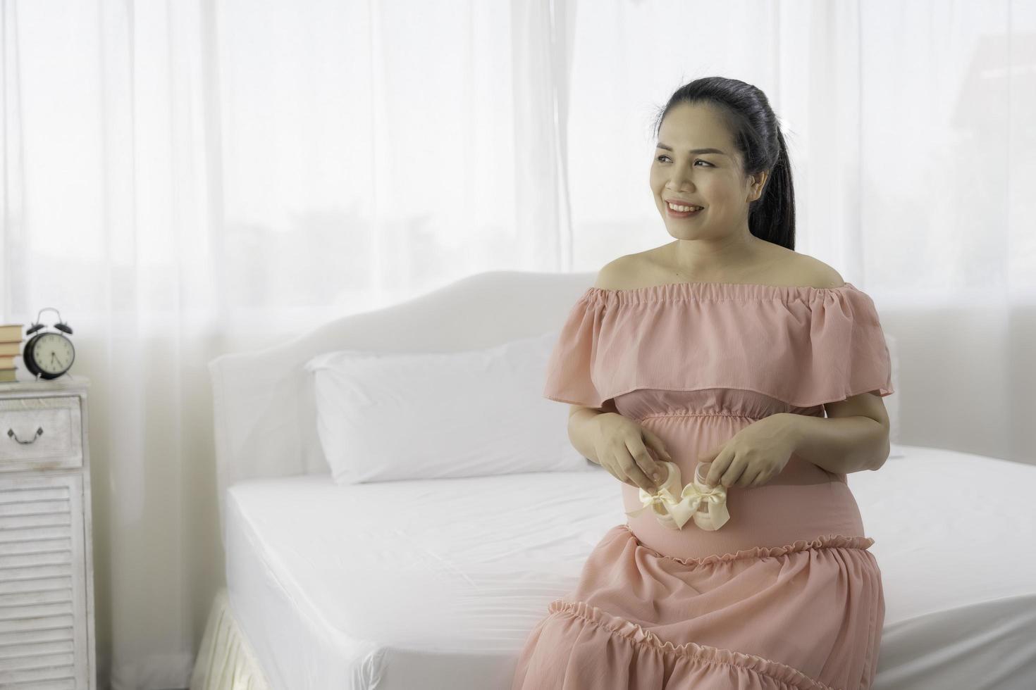mujer embarazada asiática en vestido foto