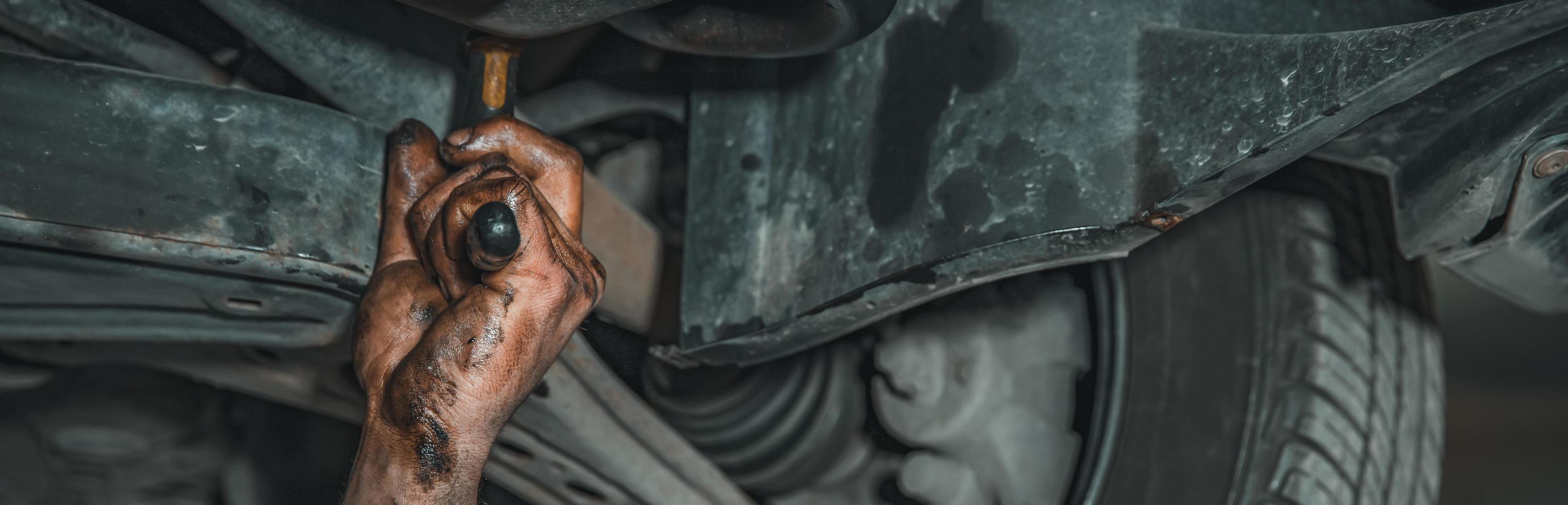 Greasy mechanic hand reaches under hood photo