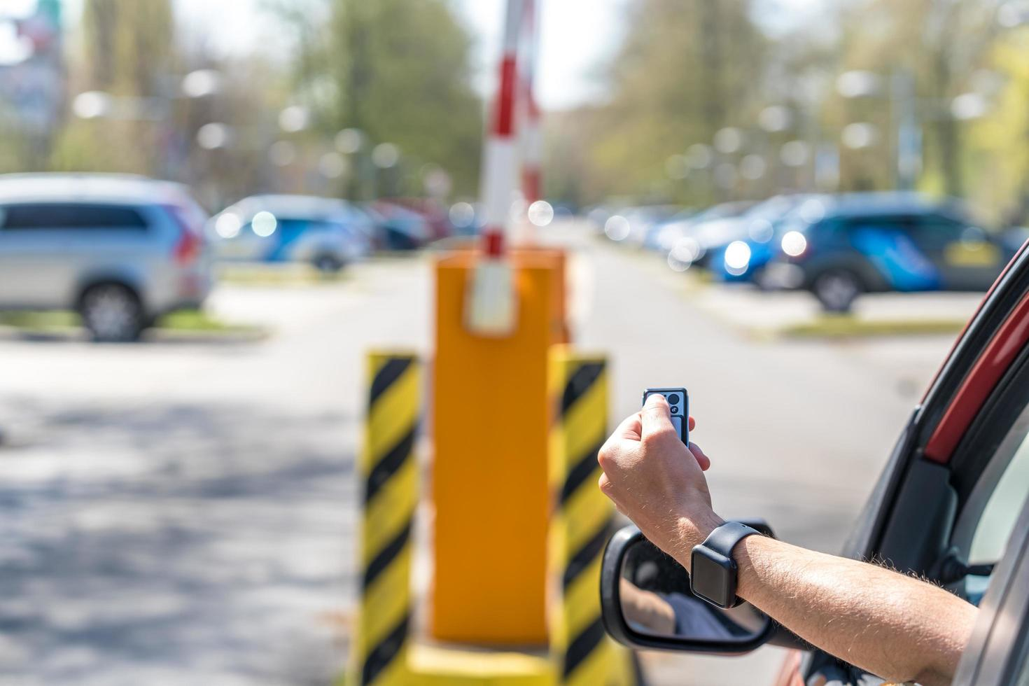el conductor del automóvil levanta la barrera de estacionamiento para salir del lote foto
