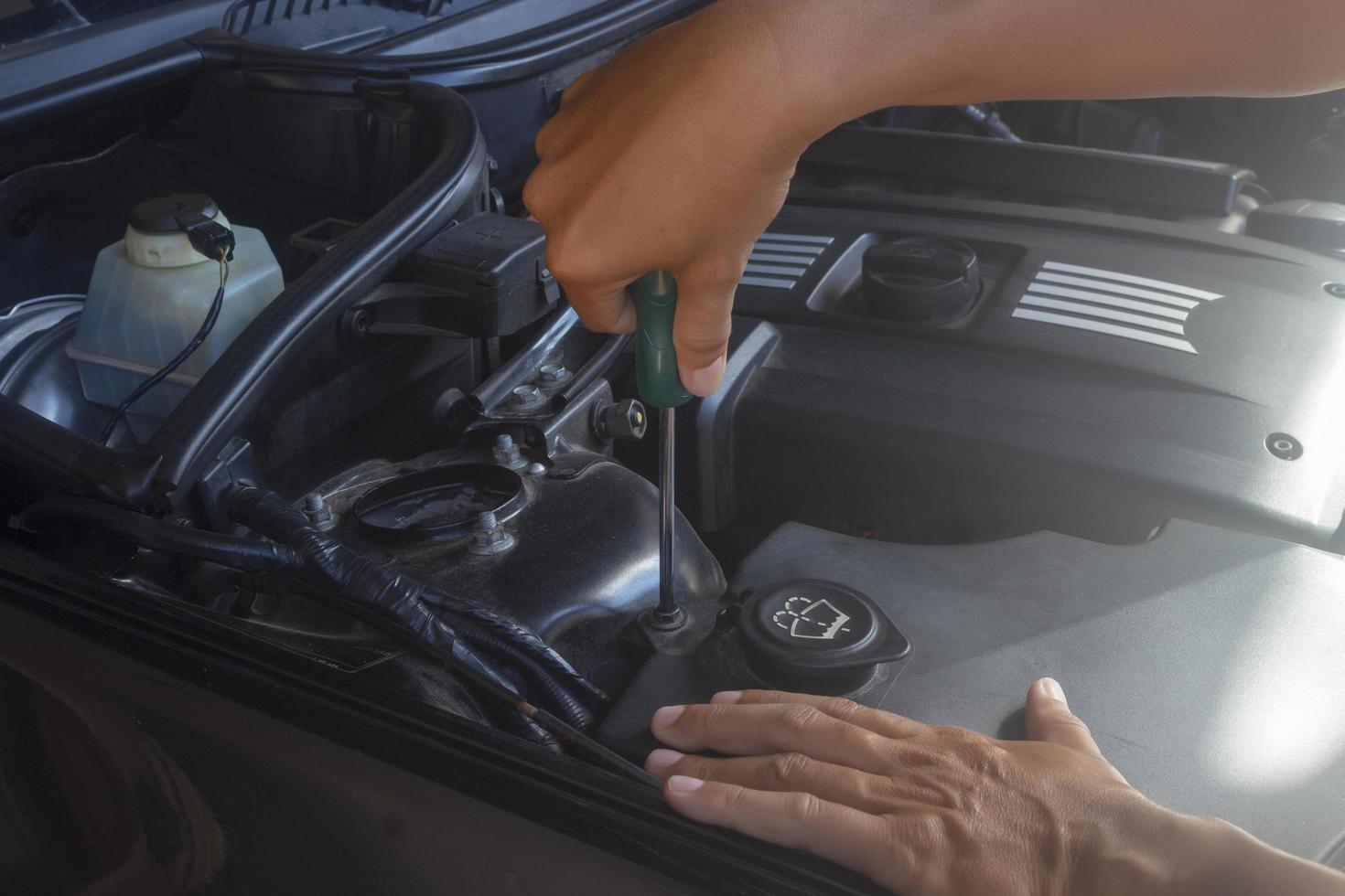 Mechanic checks under hood photo