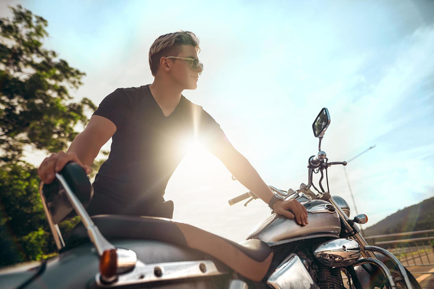 Motorcyclist stands next to bike, backlit by sun photo