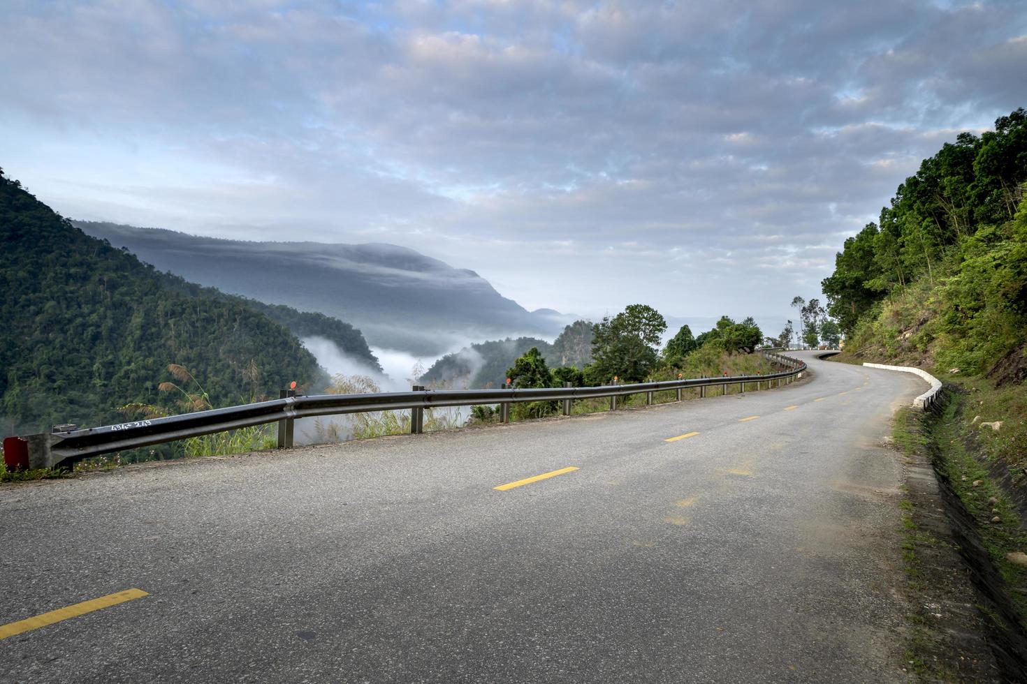 Road next to foggy forest and mountains with cloudy sky photo