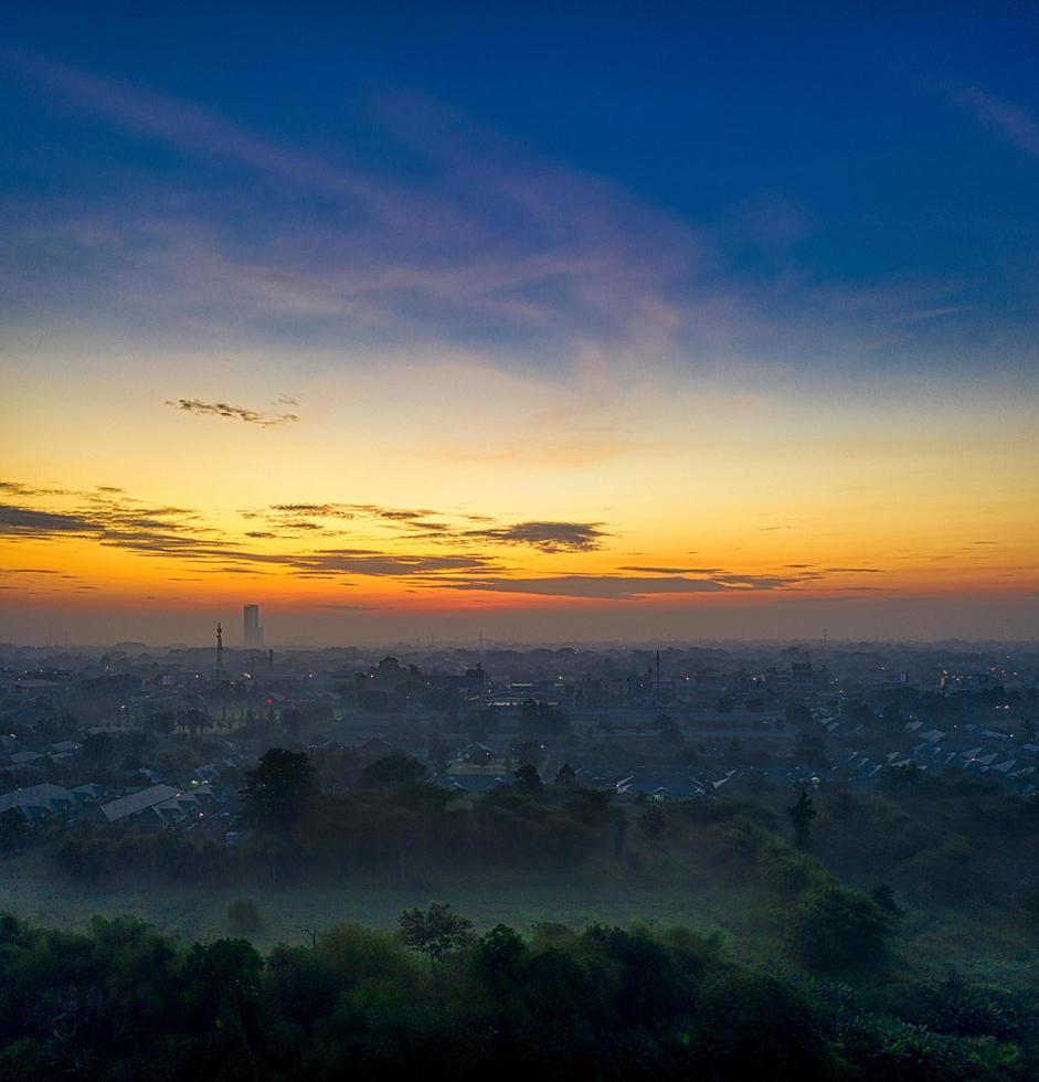 Sunset over foggy city photo