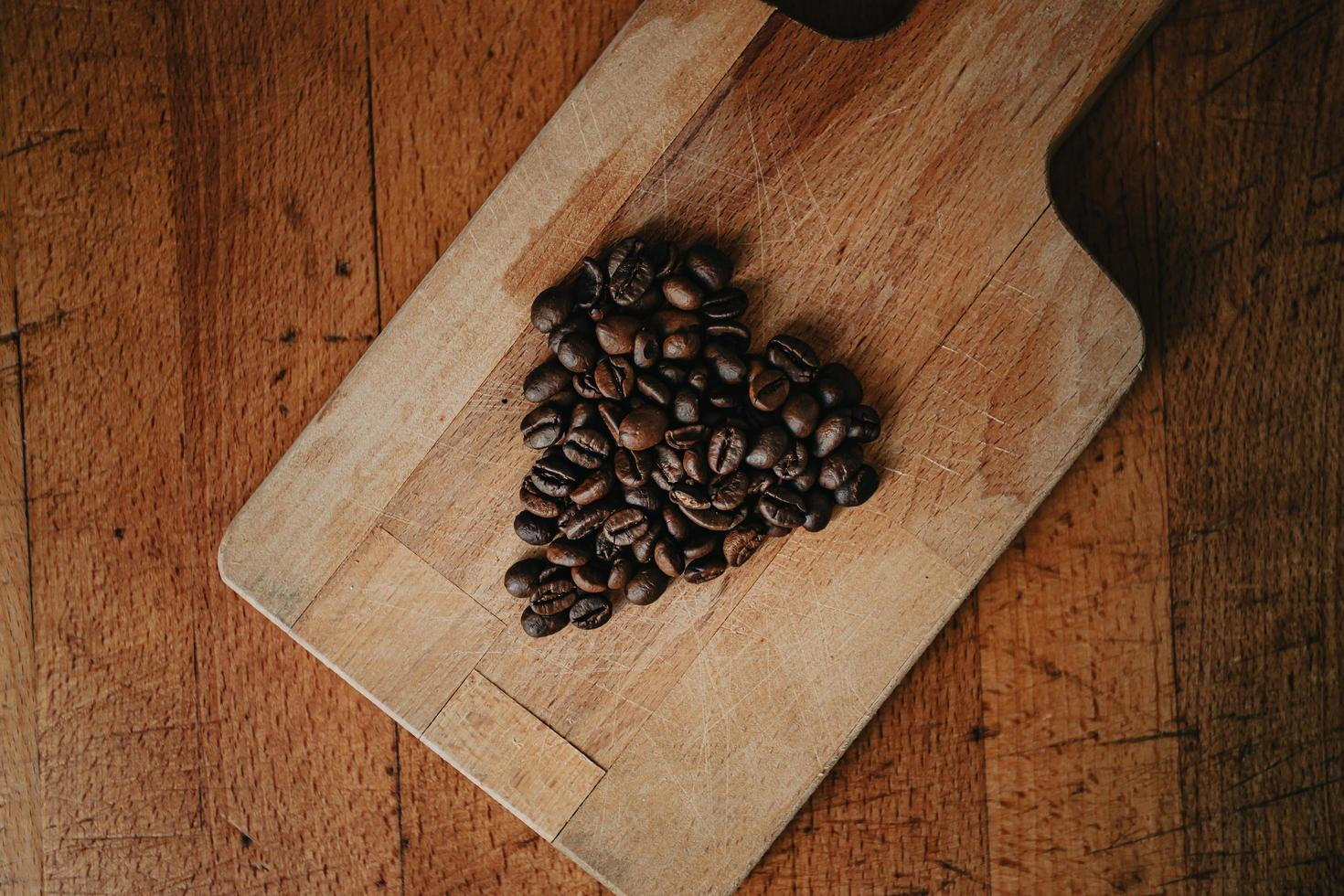 Coffee beans on cutting board on wooden table photo