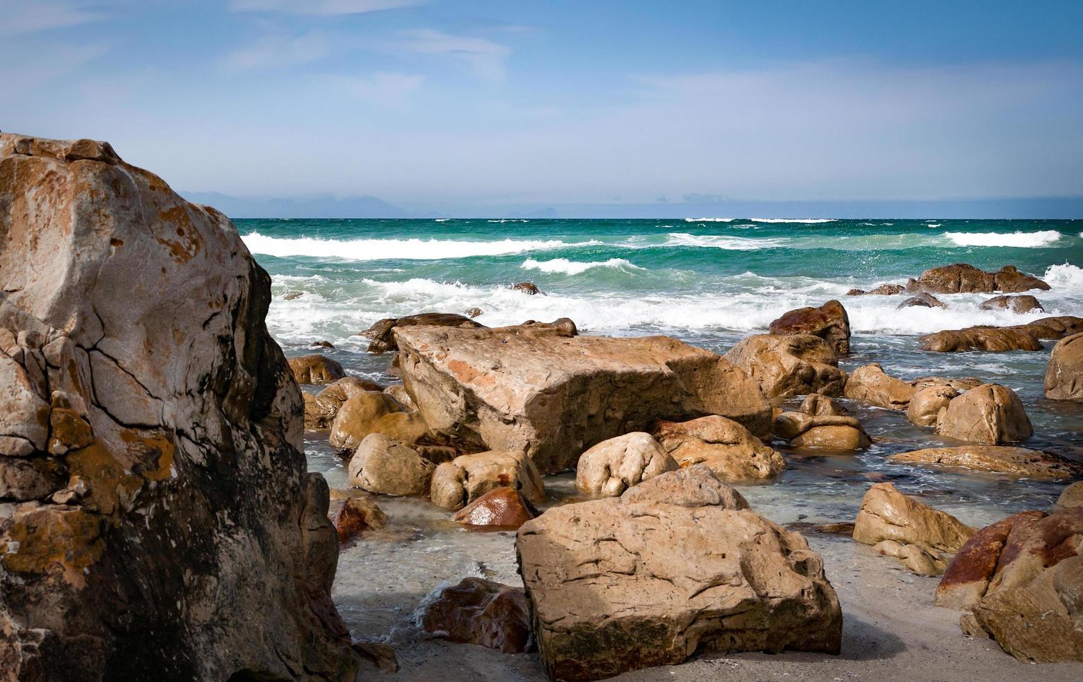 Seashore with rocks under blue sky photo