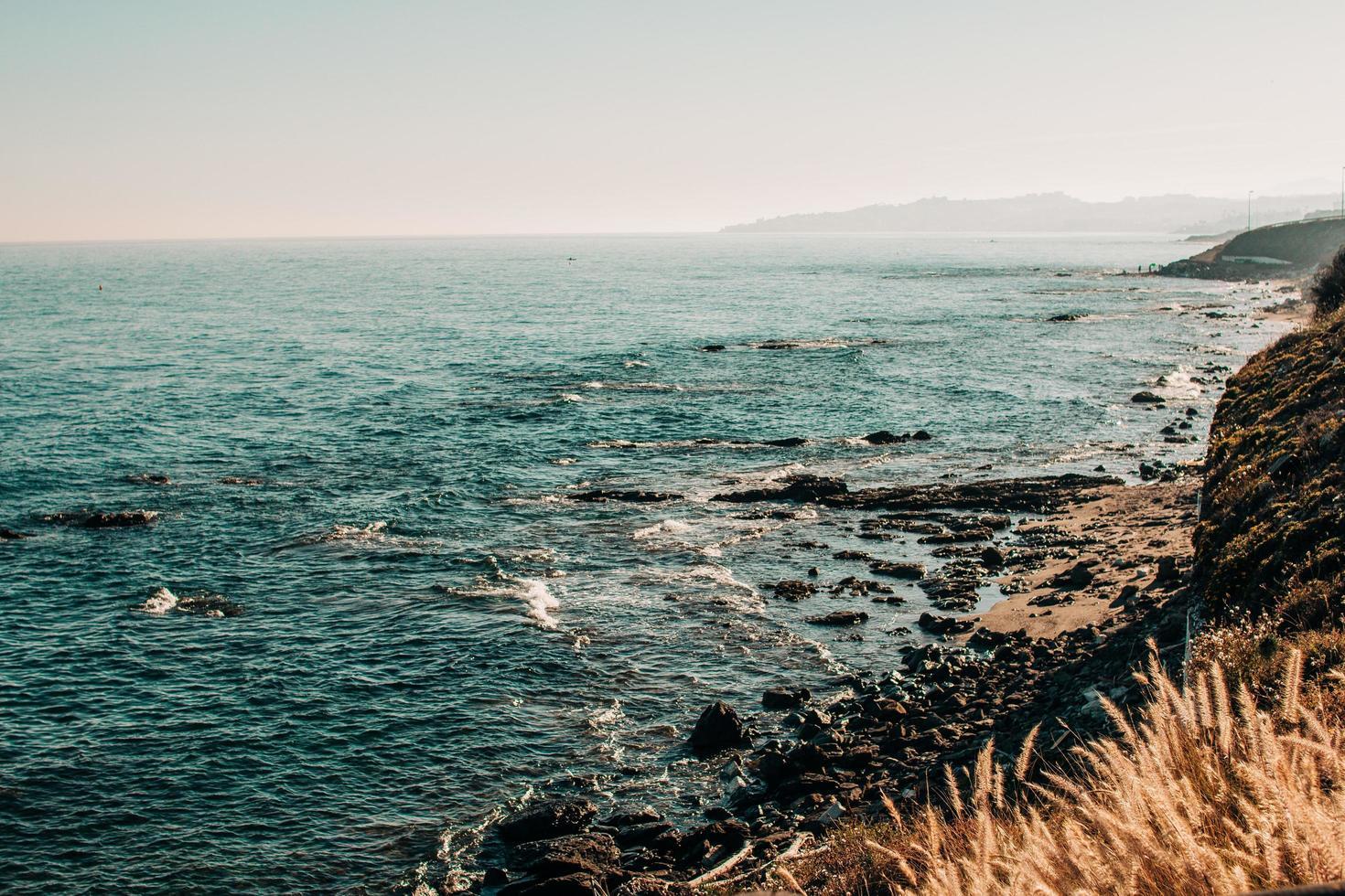 olas oceánicas rompiendo en las rocas foto