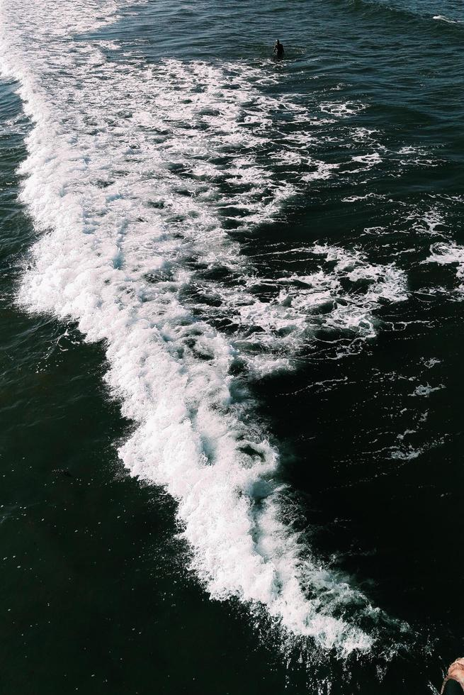 Aerial of person standing among waves photo