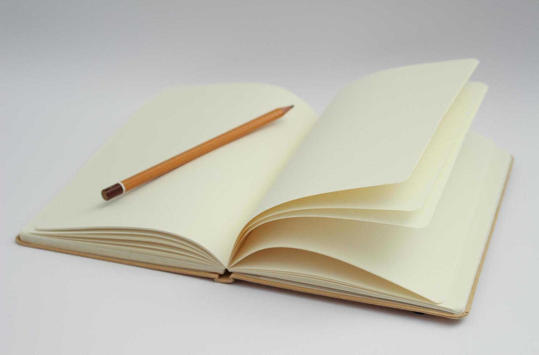 cuaderno blanco y lápiz amarillo foto