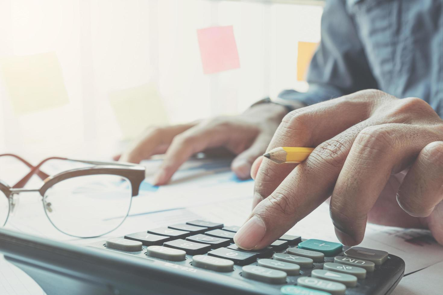 primer plano del empresario usando la calculadora en el escritorio foto