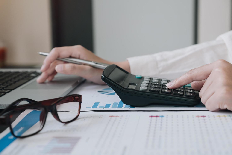 Close-up of professional using calculator photo
