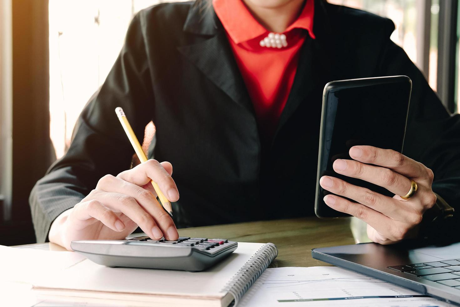 Businesswoman looking at smartphone and using calculator photo