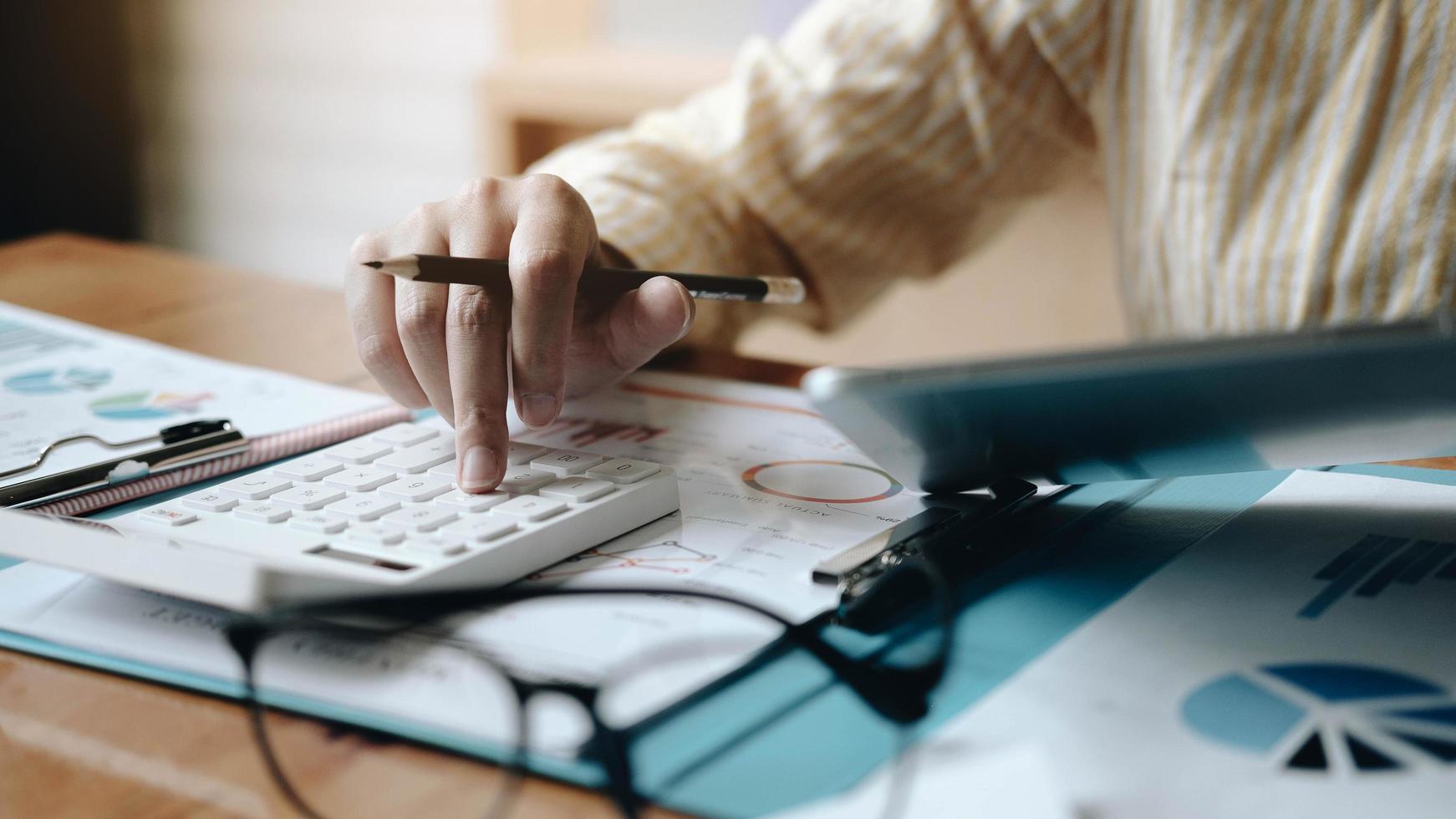 Contabilidad de la mujer mediante el cálculo y el trabajo con la computadora portátil en la oficina de escritorio, concepto de finanzas foto
