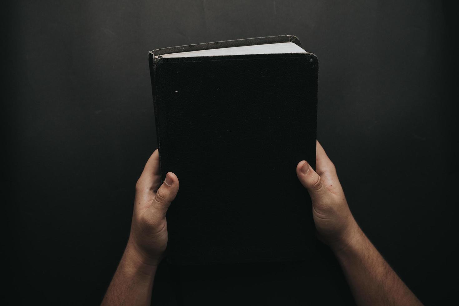 persona con libro negro foto