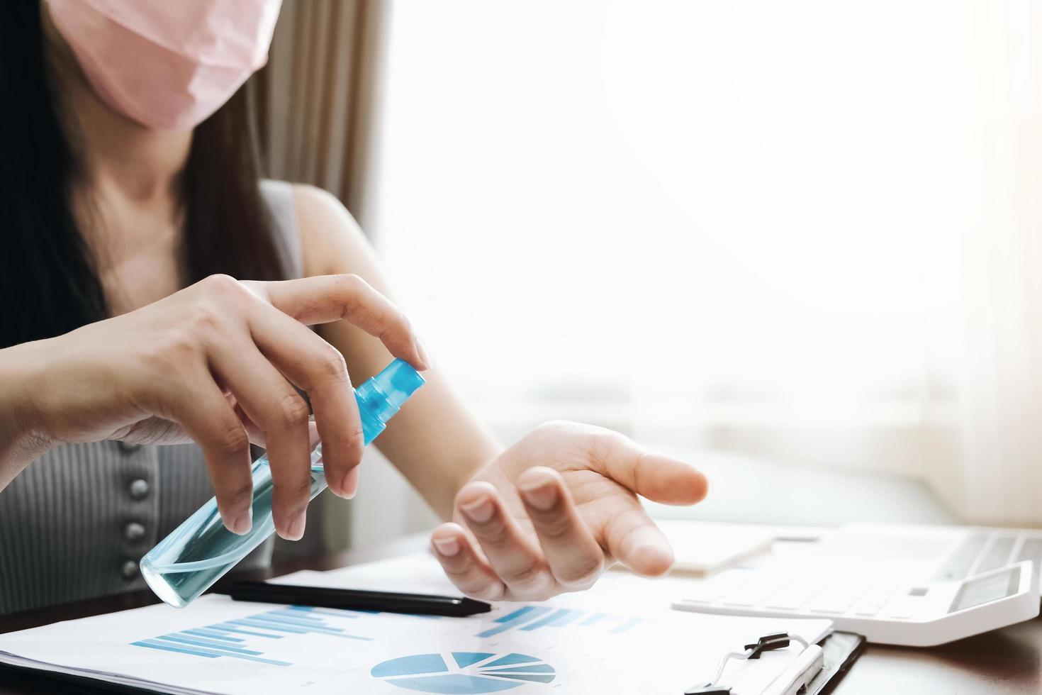 Mujer desinfectando las manos y usando mascarilla en la oficina en casa foto
