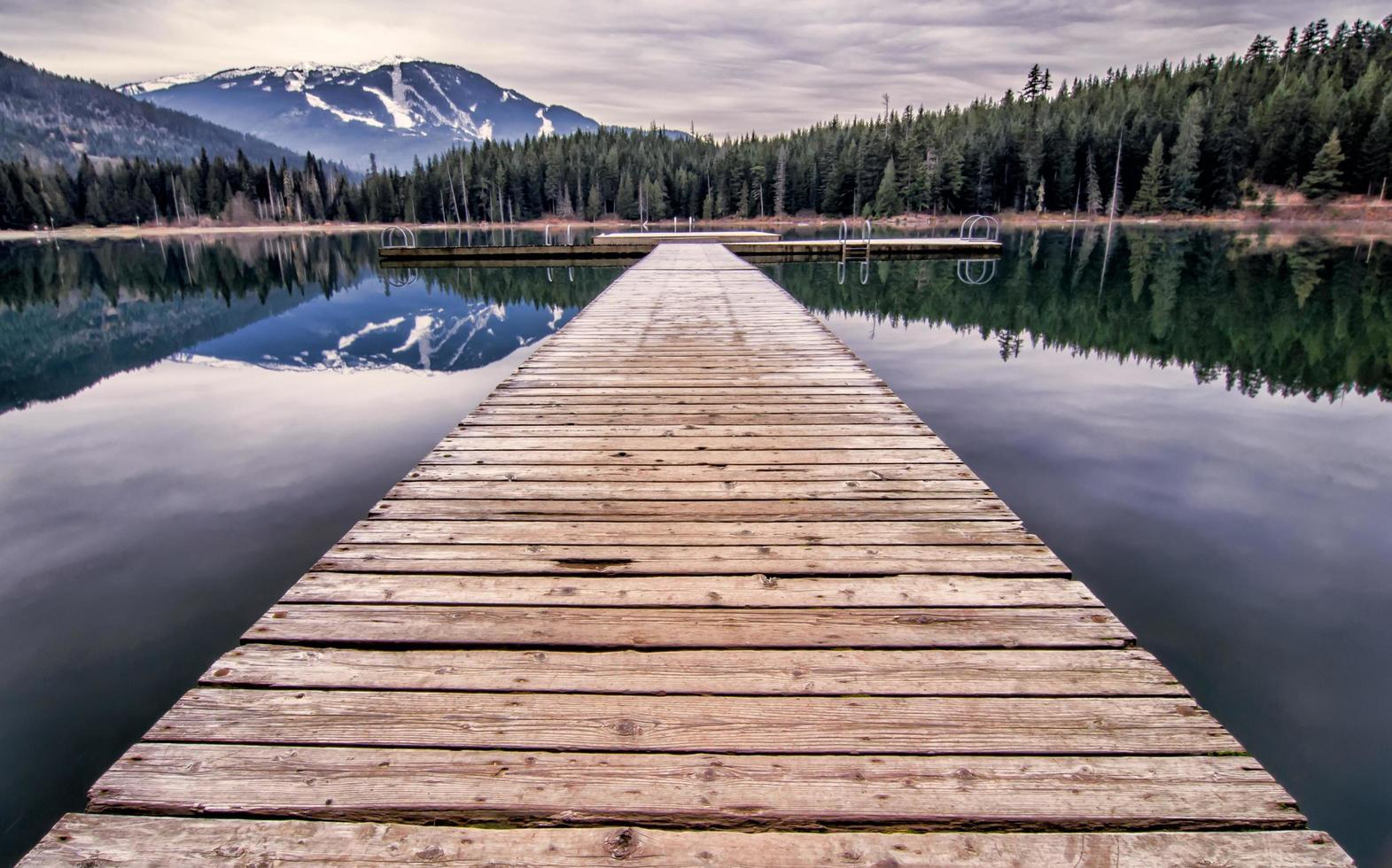 Wooden dock at lake during day photo