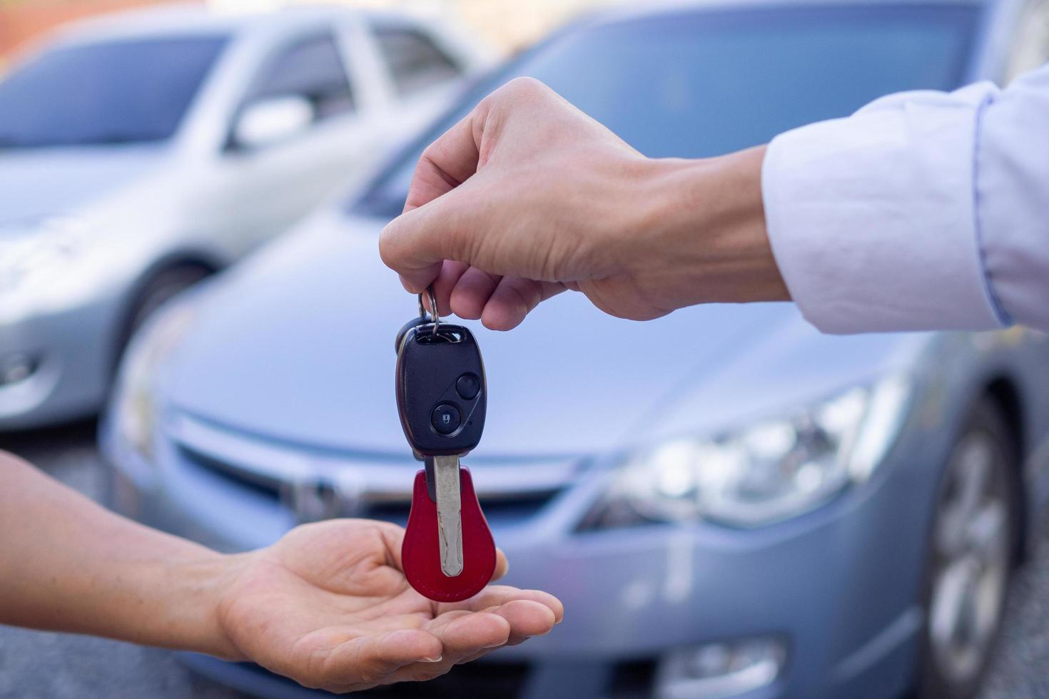 A car salesman handing a key to a  new vehicle owner photo