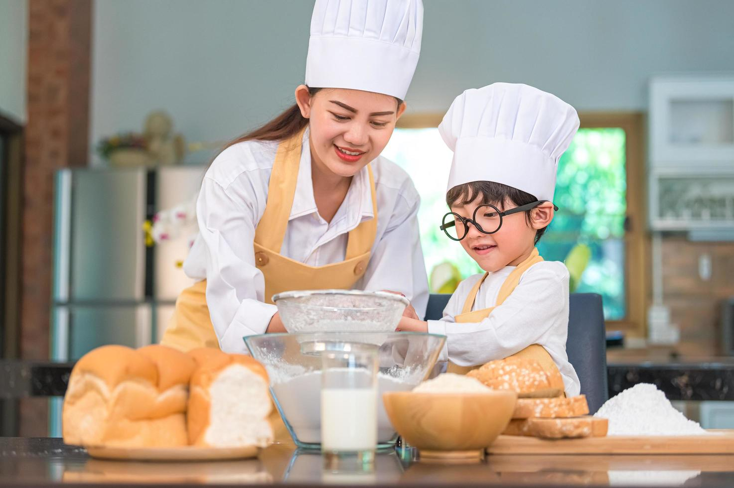 Asian boy and mother baking together photo