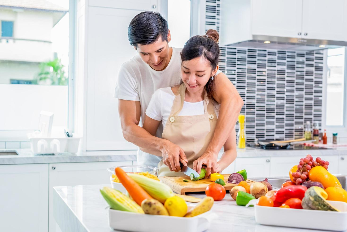 Asian couple cooking in kitchen together photo