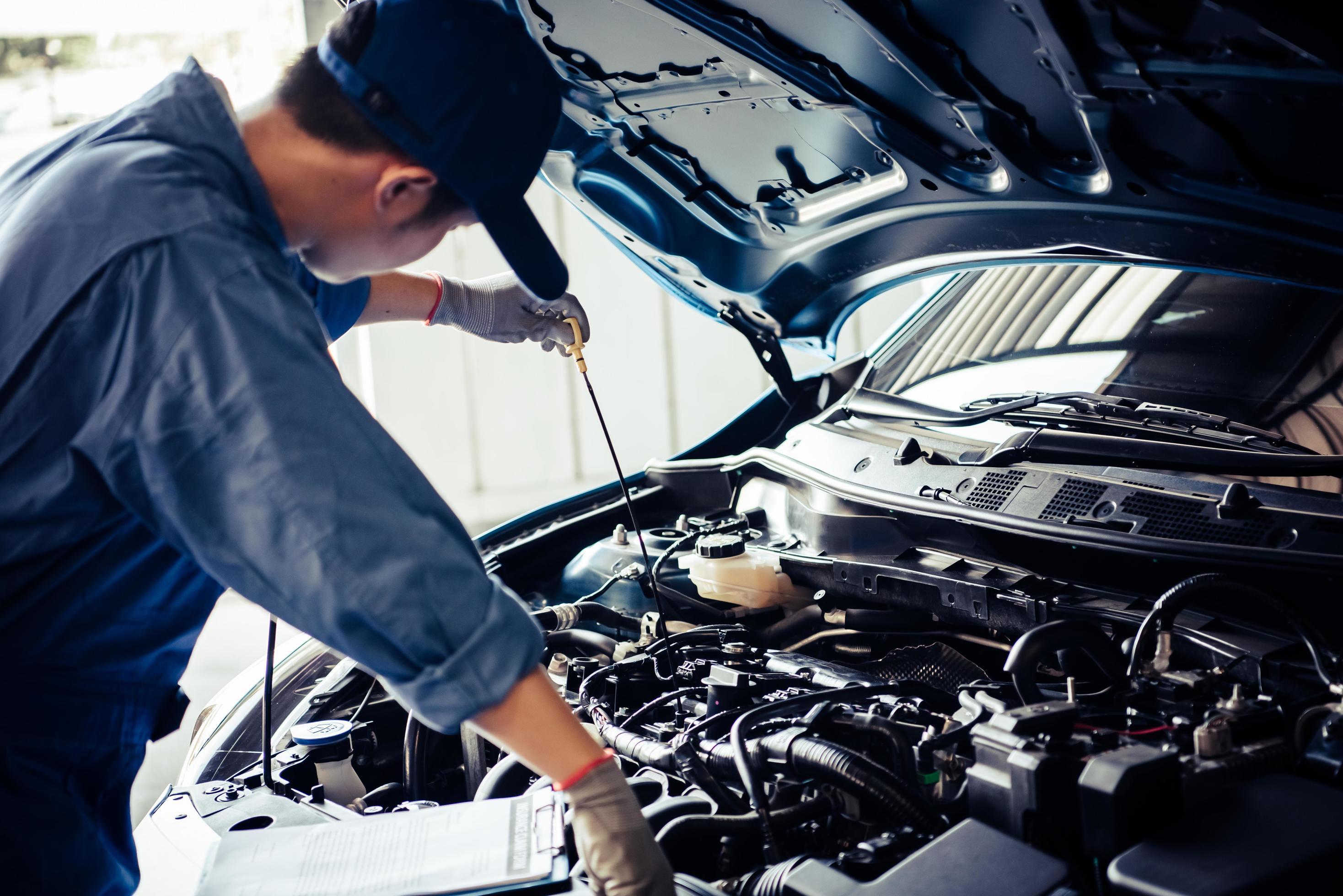 Car mechanic is conducting an inspection on vehicle Stock Photo