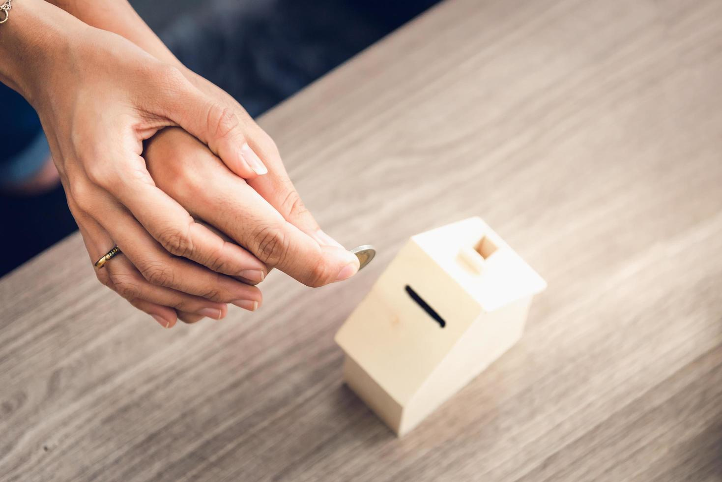 Couples hands depositing a coin into bank  photo