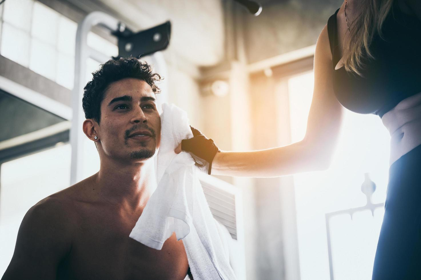 Woman wipes sweat from man's face photo