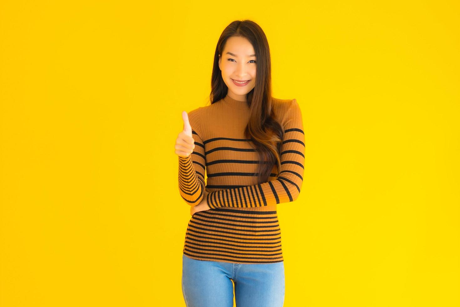 Asian woman gives thumbs up  in front of yellow background photo