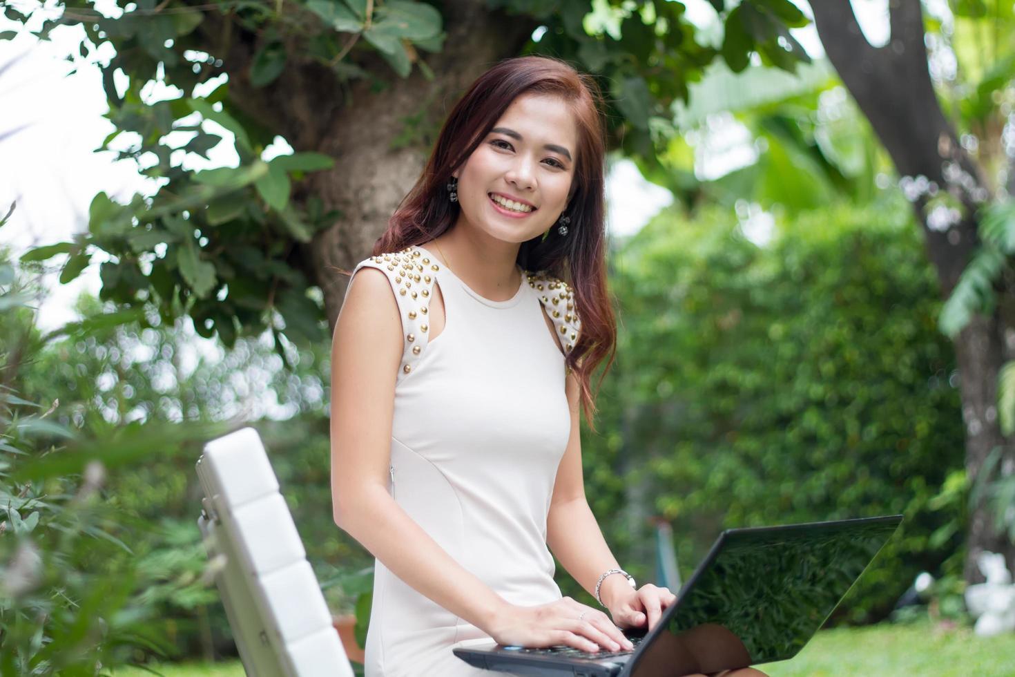 Woman using laptop outside photo