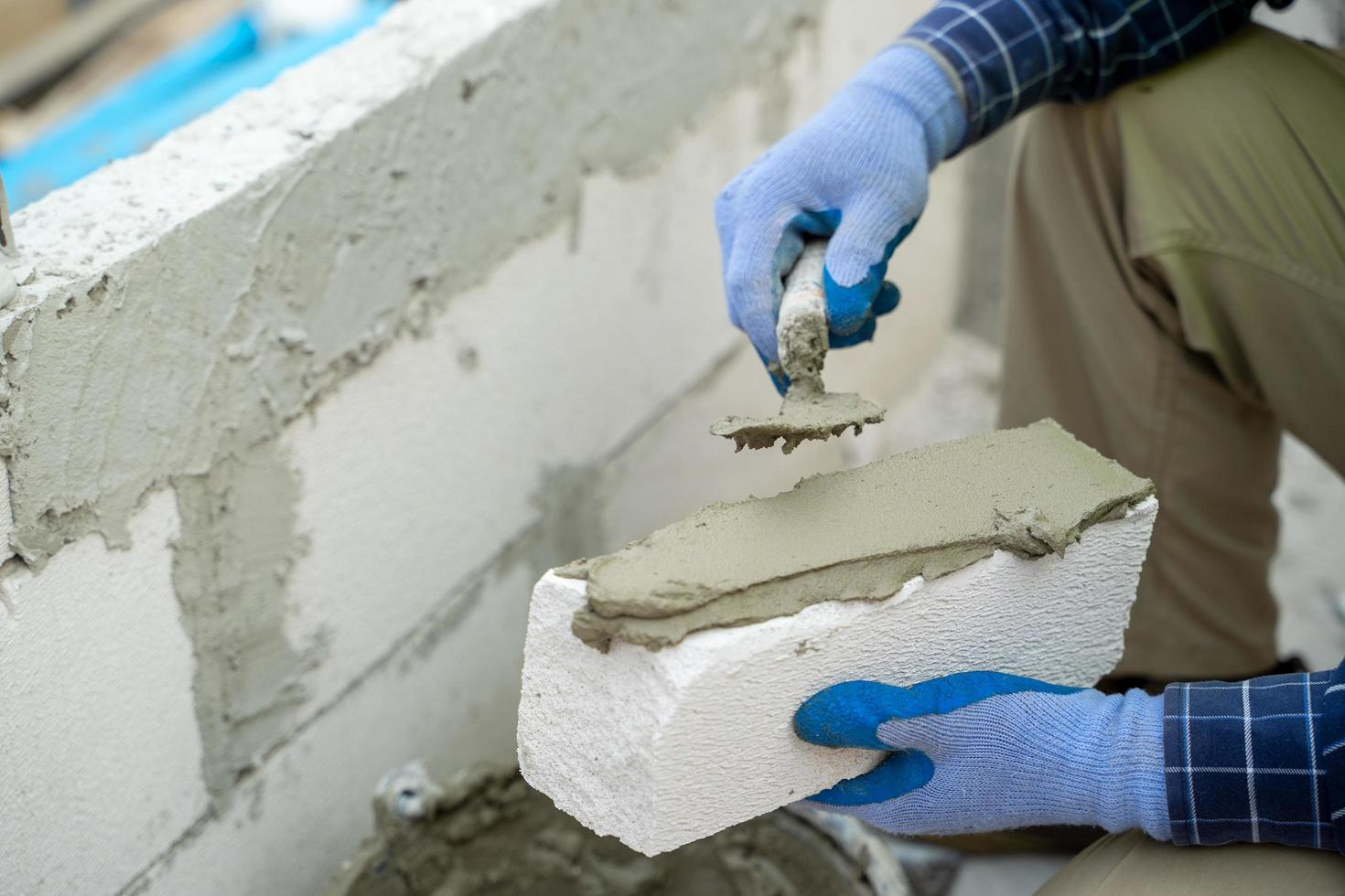 Construction worker applying plaster to a brick  photo