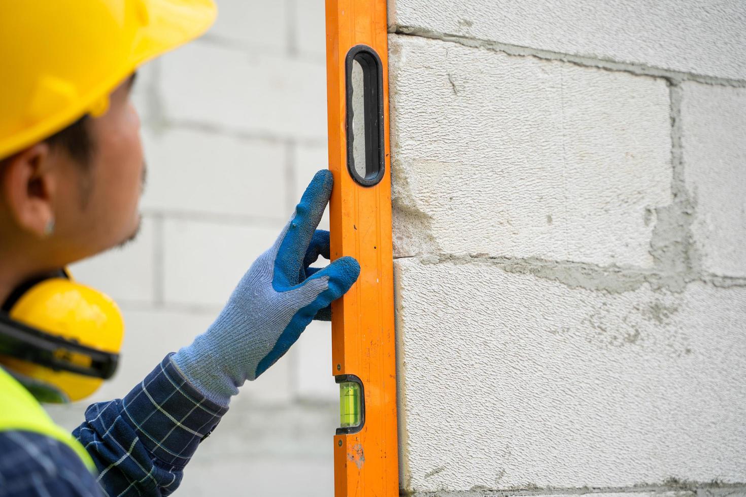 Captura recortada de un trabajador de la construcción comprobando el nivel en la pared de ladrillo foto