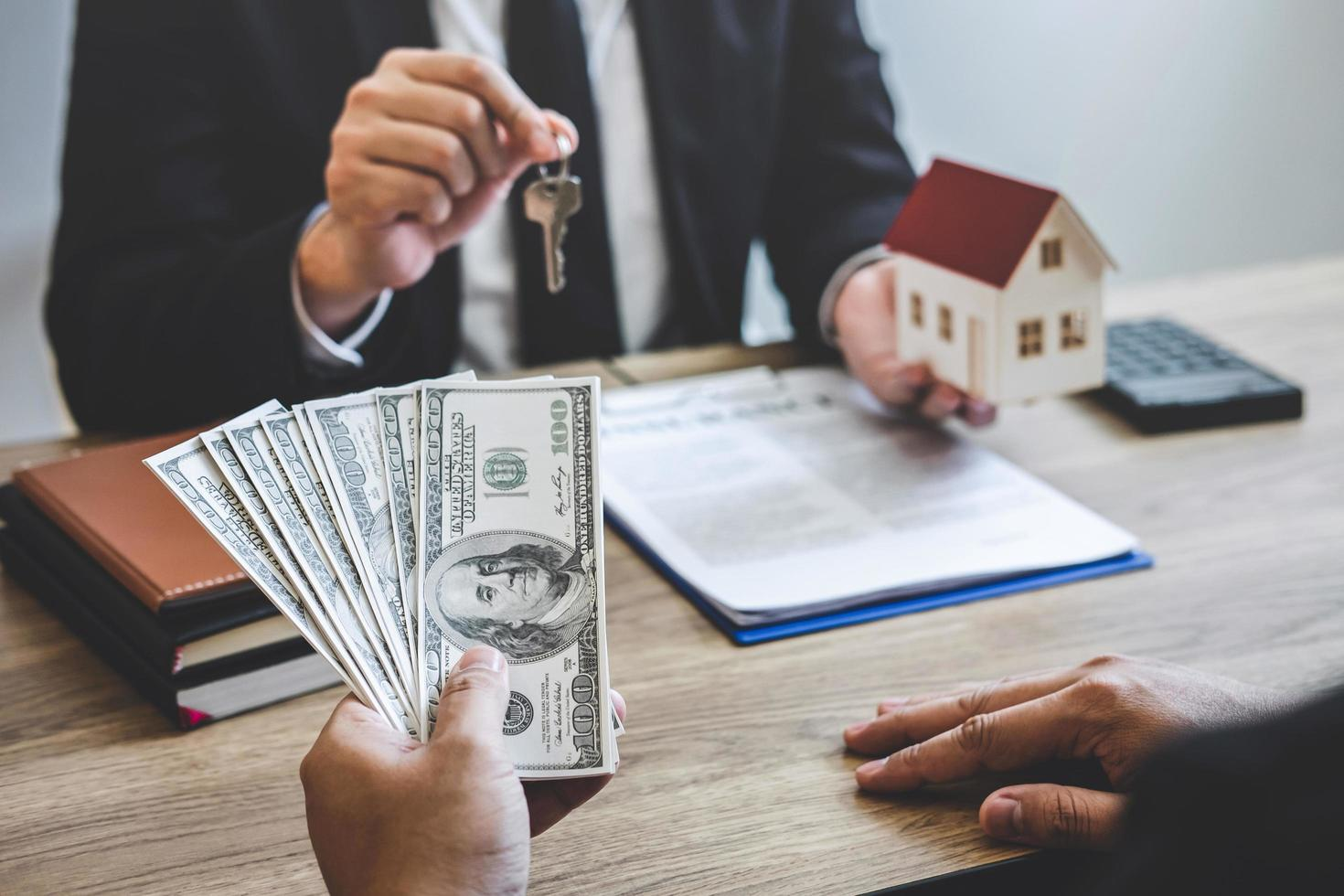 Real estate agent exchanges house key for payment photo