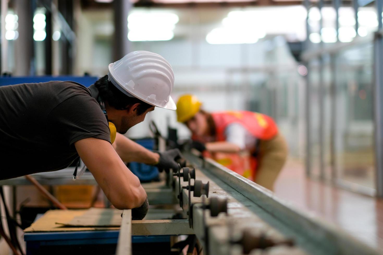 técnico masculino en planta industrial trabajando junto a compañera de trabajo foto