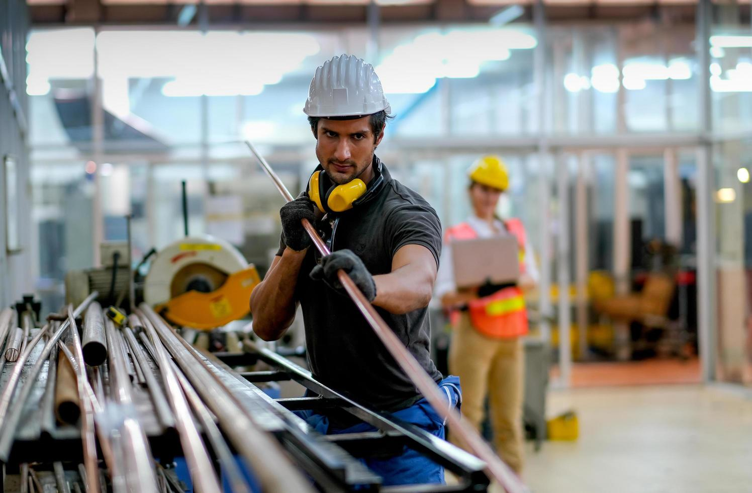 Técnico con tubos de cobre en el lugar de trabajo industrial foto
