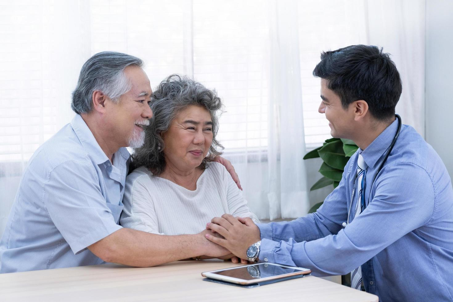 An elderly couple sits with their doctor  photo