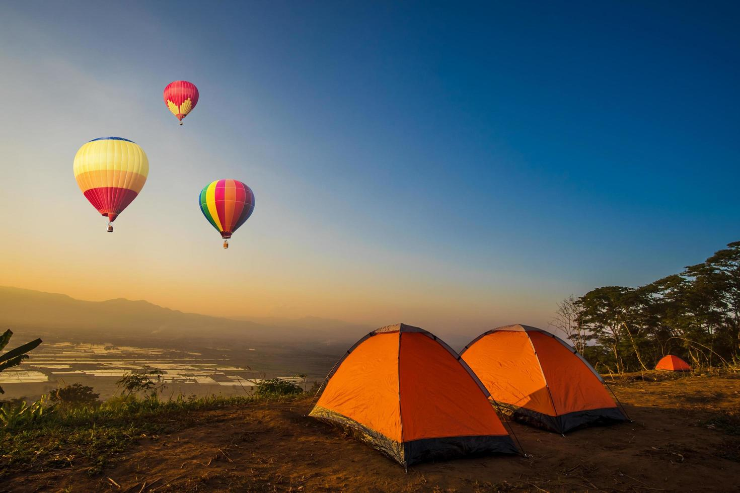 Hot air balloons flying near camping tents  photo