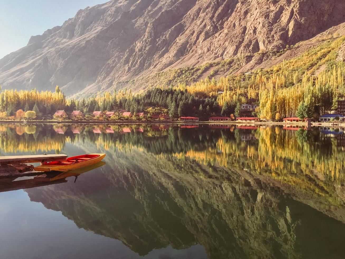 View of docked boat on still water with mountains in background photo